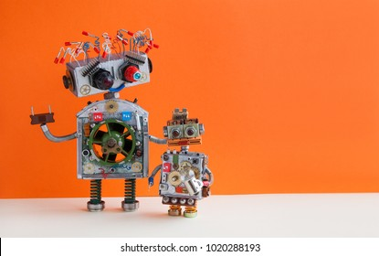 Creative design Robotic family. Big robot electrical wire hairstyle, plug arm. Small kid cyborg with lamp bulb toy. Copy space, orange wall background.