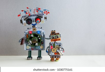 Creative design Robotic family. Big robot electrical wire hairstyle, plug arm. Small kid cyborg with lamp bulb toy. Copy space, gray wall background
