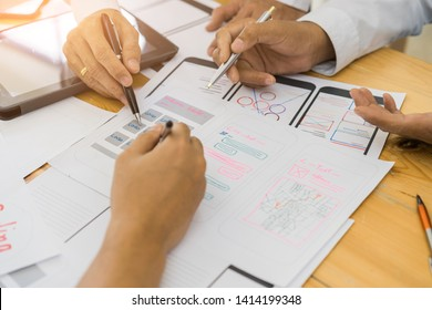Creative designer brainstorming about sketch and programming code website wireframe on smartphone application layout. ui ux designer designing smartphone application layout.