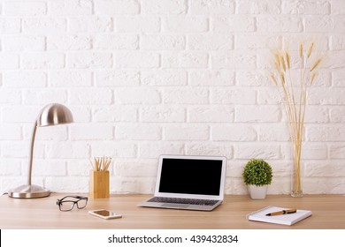 Creative designer desktop with blank laptop, stationery items, table lamp, glasses, smartphone and plants on white brick wall background. Mock up