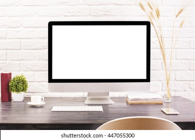 Creative designer desktop with blank white computer monitor, keyboard, coffee cup, smartphone, stationery and decorative plants on white brick wall background. Mock up