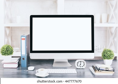 Creative designer desktop with blank white computer monitor, keyboard, stationery items, decorative plants, coffee cup and other items with shelves in the background. Mock up