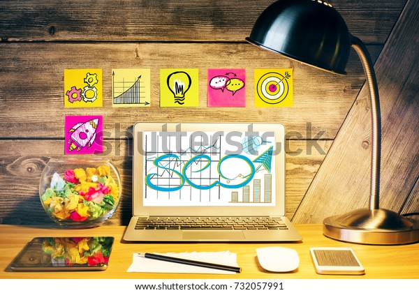 Creative designer desktop with table lamp, SEO sketch on laptop scree, various devices and stickers with rocket icons on wooden wall. SEO and media concept