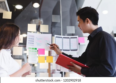 Creative designer team hands sketching of screens for mobile responsive website development with UI/UX. Developing wireframe sketch layout design mockup on smartphone screen.