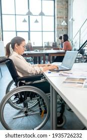 Créateur en fauteuil roulant utilisant un ordinateur portable tout en travaillant sur des croquis pour une nouvelle collection saisonnière