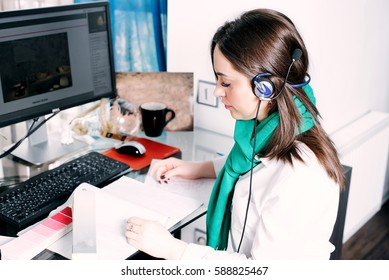 creative designer woman using headphones and working on a computer at home. student, call center, designer, work online concept
