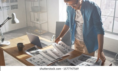 Creative Designer Works on a Storyboard, Looks at His Sketches and Concepts, Choosing the Best Drawings for His Project. Video Editing, Comics Compilation, Application UI or Game Plot. High Angle