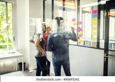 Creative designers discusing in front of glass wall using post it notes and stickers. Seen through glass in Startup office.