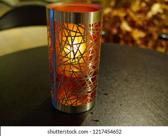 Creative desing candle holder made with metal and colorful glass glowing on a restaurant table