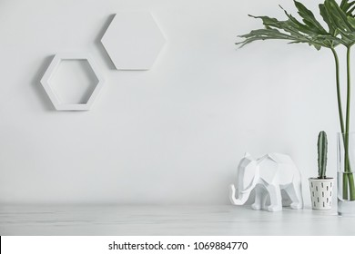 Creative desk with copy space , cacti, elephant and modern leafs. White wall with hexagone shapes.