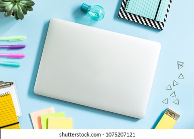 Creative desk with laptop, office accessories and suculent. Blue background.