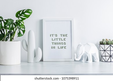 Creative desk with mock up white frame, cacti, elephant figure and plant. White wall background. Modern interior.