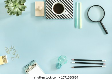 Creative desk with office accessories, cup of coffe and suculent. Blue background with copy space. Solutions for project.