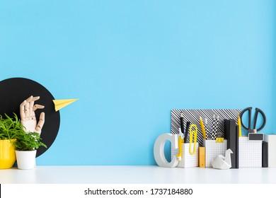 Kreativer Schreibtisch mit Schulmaterial, Pflanzen, Pinseln, gelbem Zubehör . Zurück zum Konzept der Schule.