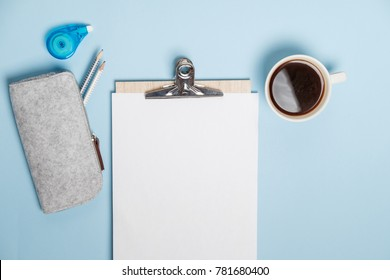 Creative desktop with laptop, coffee and stationery on blue table. Top view, Flat lay