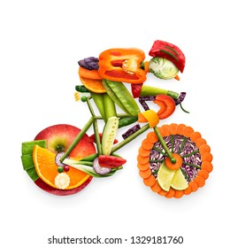 Creative diet food healthy eating concept photo of cyclist riding electric bicycle in details made of fresh fruits and vegetables full of vitamins on white background.