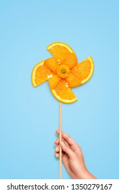 Creative diet food healthy eating concept photo of hand holding yellow toy windmill made of fresh orange slices full of vitamin on blue background.