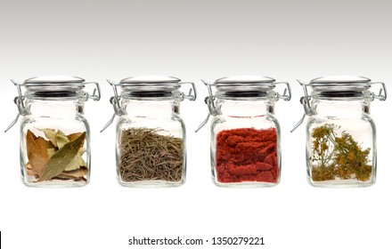 Creative diet food healthy eating concept photo of a range of four transparent glass jars of different spices and herbs on white background.