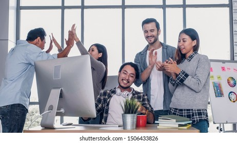 Creative director team applause for good solution of project with designer at meeting table with desktop computer.discussion idea in creative office
