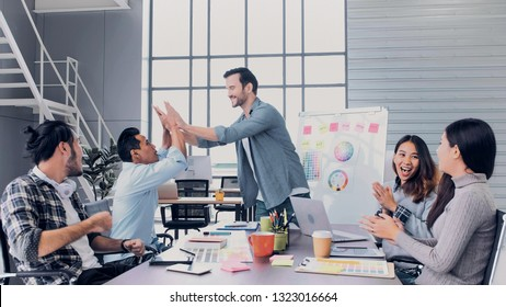 Creative director team lead clap hand with designer team at meeting table.discussion idea in creative office