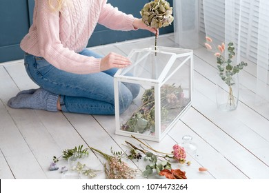creative dried flower arrangement in a glass box. beautiful room decor. woman creating an installation