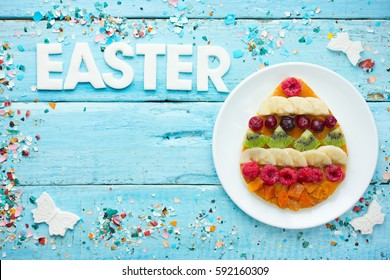 Creative Easter food background - Easter egg pancakes with fruit and berries on a blue wooden background with colorful sprinkles top view of empty space for text