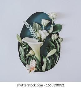 Kreatives Osterlayout mit Blumen und Blättern auf weißem Hintergrund. Frühjahr Natur Ostern Urlaub minimales Konzept. Ei Form flach gelegt.