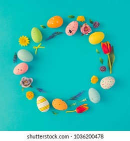 Creative Easter layout made of colorful eggs and flowers on blue background. Circle wreath flat lay concept.