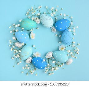Creative Easter layout made of eggs and flowers on blue background. Circle wreath flat lay concept