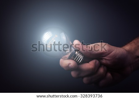 Creative enlightenment, understanding and generating new ideas, innovator and inventor with hand holding light bulb, retro toned image, selective focus.