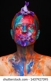 Creative fantastic makeup using colorful paints on the model. Studio beauty photoshoot