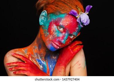 Creative fantastic makeup using colorful paints on the model. Studio beauty photoshoot
