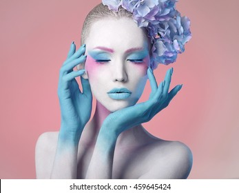 creative fashion beauty portrait of beautiful young woman with flower hairstyle. model girl with professional make-up and body art over pink background