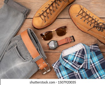 Creative fashion design for men casual clothing set on wooden background include brown boots, plaid shirt, watch, sunglasses, jeans, and belt leather. Top view