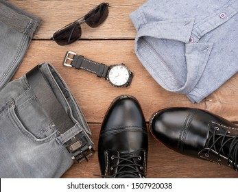 Creative fashion design outfits for men casual clothing set on wooden background include black boots, gray shirt, watch, sunglasses, jeans and belt leather. Top view