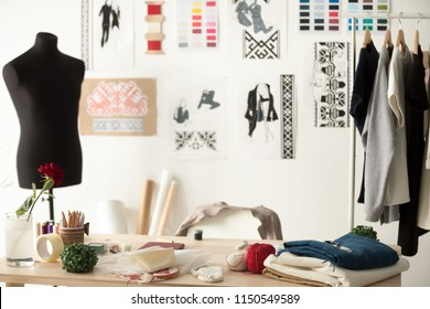 Creative fashion designer desk or workplace with sewing equipment, fabrics, templates, modern stylist inspirational office, dressmaker atelier with mannequin and clothes on hangers, couturier showroom