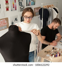 Creative fashion designers team working in clothes design studio together, man drawing sketches while woman taking dummy measurements with tape, teamwork in tailor shop or dressmaking workshop