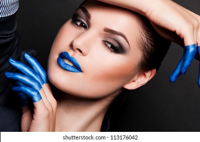 creative fashion photo of sexy woman with blue lips and blue fingers