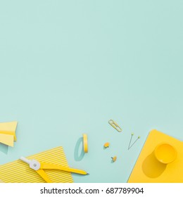 Creative, fashionable, minimalistic, school or office workspace with yellow stationery on cyan background. Flat lay.