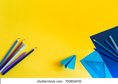 Creative, fashionable, minimalistic, school or office workspace with blue supplies on yellow background. Flat lay.