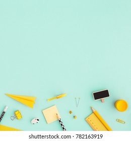 Creative, fashionable, minimalistic, school or office workspace with yellow supplies on cyan background. Back to school. Flat lay.