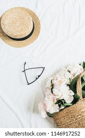 Creative female concept with white peony flowers bouquet in straw bag, glasses and straw hat on white background. Flat lay, top view fashion or beauty blog template.