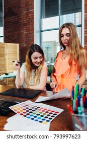 Creative female interior decorator working with a customer in her office choosing colors for a new design using color charts