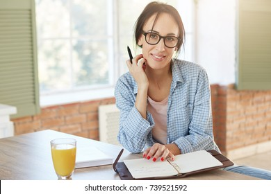 Creative female worker being at home, writes notes and plans her schedule, looks into camera. Woman freelancer works remotely, sits in kitchen. Young housewife thinks about cooking supper or dinner