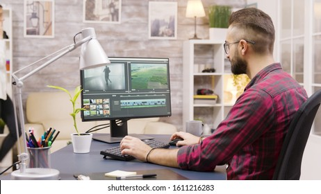 Creative filmmaker working on post production of a movie while working from home. Girlfriend in the background is walking in the house and talking on the phone.