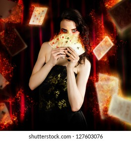 Creative Fine Art Photo Of A Beautiful Mystic Magician Holding Flaming Cards In A Depiction Of Tarot Fortune Telling