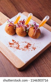 Creative fine dining: Chicken Biryani Arancini served in rice ball with sweet and spicy dip on wooden chop board.