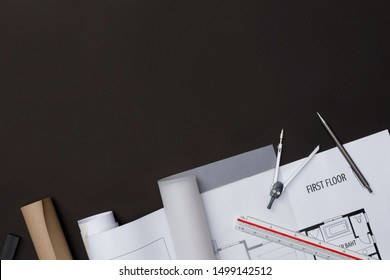 Creative flat lay of architects black table with roll blueprints, architectural project plan, engineering tools and office supplies, Workspace for new designer concept, Top view with copy space
