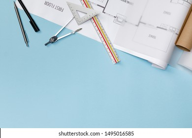 Creative flat lay of architects blue table with roll blueprints, architectural project plan, engineering tools, office supplies, isolated on blue background, Workspace for designer concept