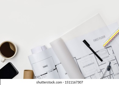 Creative flat lay of architects white table with roll blueprints, architectural project plan, engineering tools, office supplies and a cup of hot coffee,Workspace for designer concept